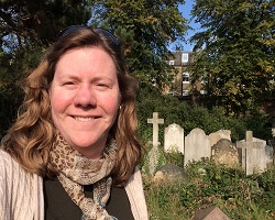 Stephanie Allen in a cemetery with headstones in the background.